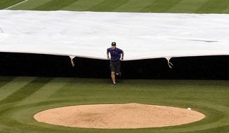 The grounds crew puts the tarp down in the third inning of a baseball game between the San Francisco Giants and the Colorado Rockies on Thursday, May 22, 2014, in Denver. The game was delayed due to thunderstorms and a tornado warning. (AP Photo/Chris Schneider)
