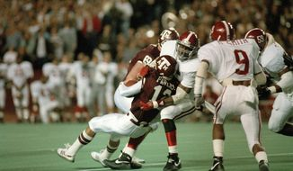 """Texas A&M quarterback Lance Pavlas (12) is sacked for a 4-yard loss by Derrick Thomas (55) of the Alabama Crimson Tide, Dec. 1, 1988. The action is from the first period of the game, dubbed the """"Hurricane Bowl"""" at College Station, Tex. (AP Photo/David Breslauer)"""