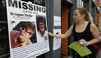 Laura Lewis, spokesperson for the family of missing University of Cincinnati student Brogan Dulle, adjusts a sign near the university campus, Thursday, May 22, 2014, in Cincinnati. Some $20,000 in rewards were being offered Thursday as the search grew for the student missing since early Sunday. (AP Photo/Al Behrman)