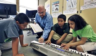 In this April 22, 2014 photo, Conrad Kehn, lead artist facilitator for the The Colorado Symphony's Very Young Composers program, helps students compose during music class, at Cole Elementary, in Denver. The Symphony's outreach program at urban schools is designed to inspire both children and professional musicians alike, and as a way for fine arts community to expose art to a young urban demographic which is often tuned in to only pop culture. (AP Photo/Brennan Linsley)