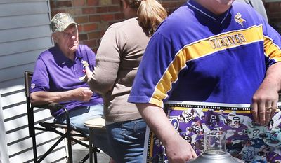 A customer, right, carries off a signed Minnesota Vikings poster as former Vikings head football coach Bud Grant, left, waits on another person during his three-day rummage sale,Thursday, May 22, 2014 at his Bloomington, Minn., home. Grant will be 87 next week. (AP Photo/Jim Mone)