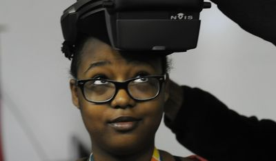 In this Friday May 16, 2014, photo, Cummins engineer Sushant Dhiman places a virtual reality headset on Greenwood Middle School student Brooklynne Wilson, 13, in Greenwood, Ind. (AP Photo/The Daily Journal, Scott Roberson)