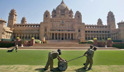 FILE - In this March 6, 2007 file photo, workers level the cricket pitch built for the wedding celebrations of British actress Elizabeth Hurley and her new husband Arun Nayar at the Umaid Bhawan Palace, the Maharaja of Jodphur's palace-turned-luxury resort in Jodhpur, India.  (AP Photo/Mustafa Quraishi, File)