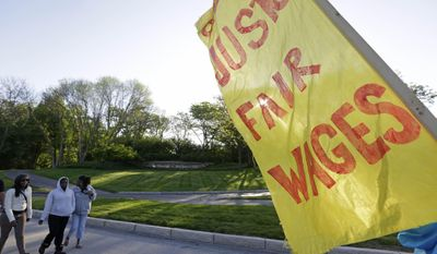 A McDonalds sign can be seen in the background as hundreds of demonstrators begin gather outside the entrance of the McDonalds Corporation, Thursday, May 22, 2014, in Oak Brook, Ill., protesting for a $15 an hour wage and the right to unionize. The group gathered outside the entrance as the company held the annual shareholders meeting. (AP Photo/M. Spencer Green)