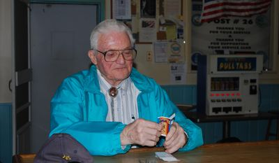In this photo taken March 21, 2014, American Legion member Bill Pearl, of Powell, opens some pull tabs at the American Legion in Powell, Wyo. Pearl said he enjoys the friends he has made at the post. The American Legion was founded by World War I veterans in France and chartered by Congress in 1919, but as its centennial approaches, the American Legion's future is uncertain. (AP Photo/The Powell Tribune, Tom Lawrence)