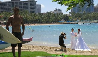 This May 21, 2014 photo shows surfer Kainoa Haas, 22, left, standing on grass fronting Duke Kahanamoku Beach  as a wedding couple is photographed in the Honolulu tourist neighborhood of Waikiki. The destination topped this year's annual ranking of the best public beaches in the United States as chosen by Stephen Leatherman, better known as Dr. Beach. (AP Photo/Sam Eifling)