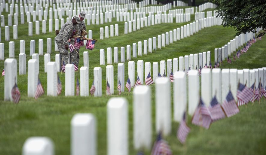 ** FILE ** Soldiers of the 3rd U.S. Infantry Regiment, also known as The Old Guard, place flags at grave sites at Arlington National Cemetery in Arlington, Va., Thursday, May 22, 2014. (AP Photo/Cliff Owen)