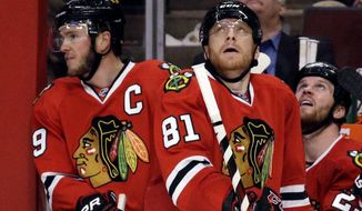 Chicago Blackhawks' Jonathan Toews, left, Marian Hossa (81) and Bryan Bickell (29) react after Los Angeles Kings' Jake Muzzin scored a goal  during the third period in Game 2 of the Western Conference finals in the NHL hockey Stanley Cup playoffs in Chicago on Wednesday, May 21, 2014. (AP Photo/Nam Y. Huh)
