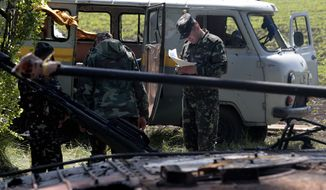 High-ranking Ukrainian officers investigate at a gunfight site near the village of Blahodatne, eastern Ukraine, on Thursday, May 22, 2014. At least 11 Ukrainian troops were killed and about 30 others were wounded when Pro-Russians attacked a military checkpoint, the deadliest raid in the weeks of fighting in eastern Ukraine. Three charred Ukrainian armored infantry vehicles, their turrets blown away by powerful explosions, and several burned vehicles stood at the site of the combat. (AP Photo/Ivan Sekretarev)