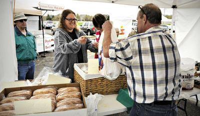 Lisa Owens, Sartell, buys bread from Steve Friedericks of College Artisan Bakery during the Sartell Farmers Market at the Sartell City Hall Monday, May  12, 2014, in Sartell, Minn. (AP Photo/The St. Cloud Times, Jason Wachter)