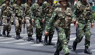 "Thai soldiers patrol near the Army Club before former Prime Minister Yingluck Shinawatra arrives to report to Thailand's ruling military in Bangkok, Thailand, Friday, May 23, 2014. The military on Friday summoned the entire ousted government and members of the politically influential family at the heart of the country's long-running conflict, a day after it seized control of this volatile Southeast Asian nation in a non-violent coup. It was unclear why more than 100 people,  including the ousted prime minister and several members of the influential Shinawatra family, were ordered to report to the military, which said it was summoning the high-profile figures ""to keep peace and order and solve the country's problems."" (AP Photo/Sakchai Lalit)"