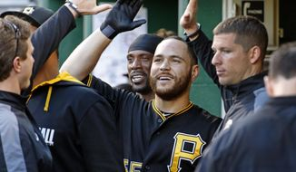 Pittsburgh Pirates' Russell Martin, center, celebrates in the dugout after scoring from third on a wild pitch by Washington Nationals starting pitcher Jordan Zimmermann during the second inning of a baseball game in Pittsburgh, Friday, May 23, 2014. (AP Photo/Gene J. Puskar)