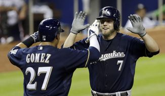 Milwaukee Brewers' Mark Reynolds (7) is greeted at home plate by teammate Carlos Gomez (27) after Reynolds hit a two-run home run against the Miami Marlins in the fifth inning of a baseball game in Miami, Friday, May 23, 2014. Gomez scored on the home run. (AP Photo/Alan Diaz)