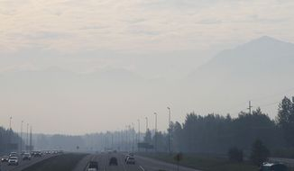 Haze from smoke covers a highway in Anchorage, Alaska, Thursday, May 22, 2014. Residents in Anchorage woke up Thursday to a smokey haze and the smell of a campfire over the state's largest city. The smoke is from wildfires burning on Alaska's Kenai Peninsula. (AP Photo/Mark Thiessen)
