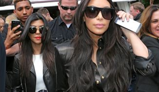 Kim Kardashian, front and Kourtney Kardashian, left, leave at a restaurant in Paris, Thursday, May 22, 2014. The gates of the Chateau de Versailles, once the digs of Louis XIV, will be thrown open to Kim Kardashian, Kanye West and their guests for a private evening this week ahead of their marriage (AP Photo/Jacques Brinon)