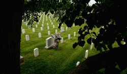 Army Private Tobias Tirrell with the Third U.S. Infantry Regiment (The Old Guard) places a small American flag at a grave marker to honor the nations fallen members of the military at Arlington National Cemetery, Washington, D.C, Thursday, May 22, 2014. The Old Guard placed flags for more than 220,000 graves. (Andrew Harnik/The Washington Times)