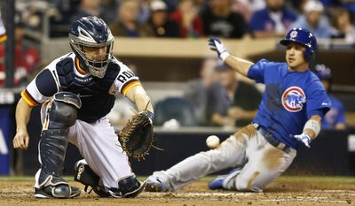 San Diego Padres catcher Nick Hundley waits on the late throw as Chicago Cubs' Darwin Barney slides in safely in the fifth inning of a baseball game Thursday, May 22, 2014, in San Diego.  (AP Photo/Lenny Ignelzi)