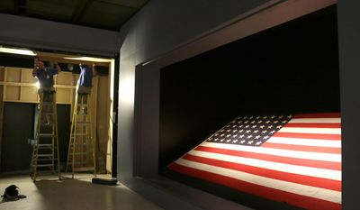 In this photo taken Wednesday, May 21, 2014, workers at the Houston Museum of Natural Science work on an exhibit spotlighting the flag from the USS Texas in Houston. The 17-by-9 foot, 48-star flag flew over the battleship on D-Day, June 6, 1944, off the beaches at Normandy. (AP Photo/Pat Sullivan)