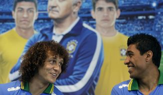 Backdropped by a picture of Brazilian coach Luiz Felipe Scolari, Brazilian soccer players  David Luiz, left, and Paulinho attend a promotional event for Gillette in Sao Paulo, Brazil, Tuesday, May 20, 2014. The World Cup will open on June 12 with a match between Brazil and Croatia at the Itaquerao Stadium in Sao Paulo. (AP Photo/Andre Penner)