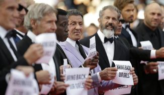 From third left, actors Harrison Ford, Wesley Snipes, Sylvester Stallone, Mel Gibson and Antonio Banderas, from the movie The Expendables 3, hold up signs as they arrive for the screening of The Homesman at the 67th international film festival, Cannes, southern France, Sunday, May 18, 2014. (AP Photo/Thibault Camus)