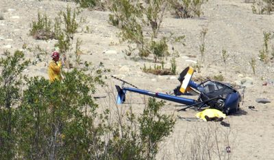 This image provided by the Santa Paula Times shows the crash site of a Robinson R22 helicopter in the Santa Clara River just west of the Santa Paula, Calif., Airport Friday May 23, 2014. The Ventura County Fire Department confirmed at least one person was killed in the crash, shown covered lower right. It appeared that the aircraft was headed to the airport when it stuck power lines and crashed. (AP Photo/Santa Paula Times, Debbie Johnson)
