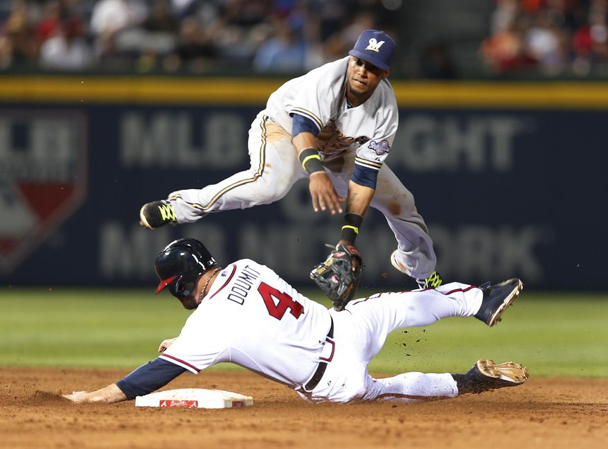 Atlanta Braves's Ryan Doumit, bottom, is safe at second base as Milwaukee Brewers shortstop Jean Segura, top, covers in the seventh  inning of a baseball game Thursday, May 22, 2014 in Atlanta. Doumit was initially called out but the call was overturned after a video review. (AP Photo/John Bazemore)