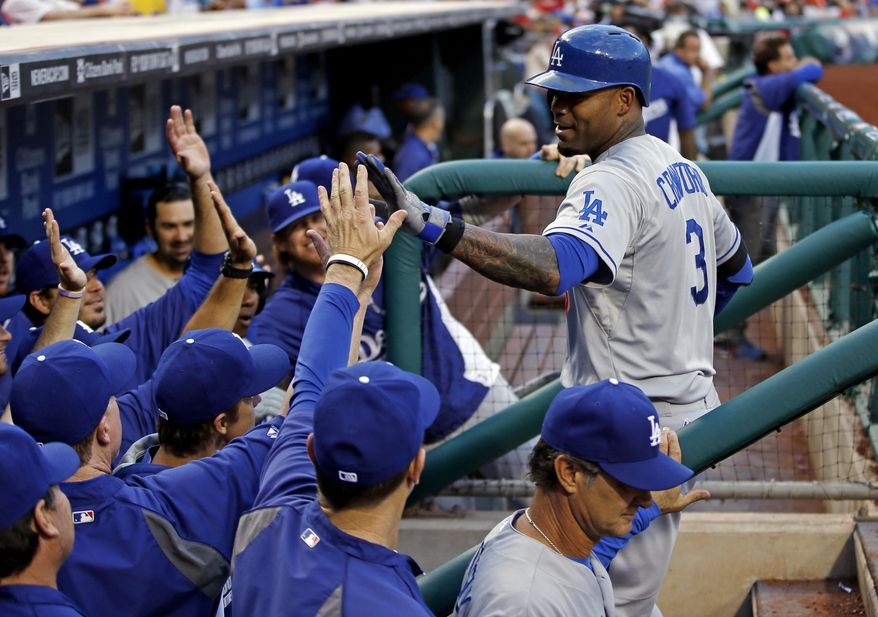 Los Angeles Dodgers' Carl Crawford is congratulated in the dugout after hitting a home run during the second inning of a baseball game against the Philadelphia Phillies, Friday, May 23, 2014, in Philadelphia. (AP Photo/Matt Slocum)