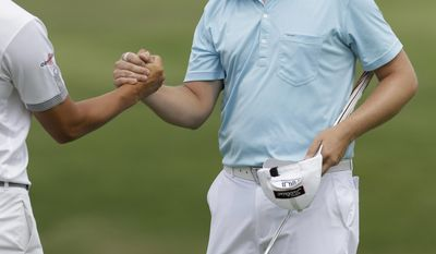 Brice Garnett, right, shakes hands with fellow golfer Danny Lee after they played the 18the hole during the second round of the PGA Colonial golf tournament in Fort Worth, Texas, Friday, May 23, 2014. (AP Photo/LM Otero)