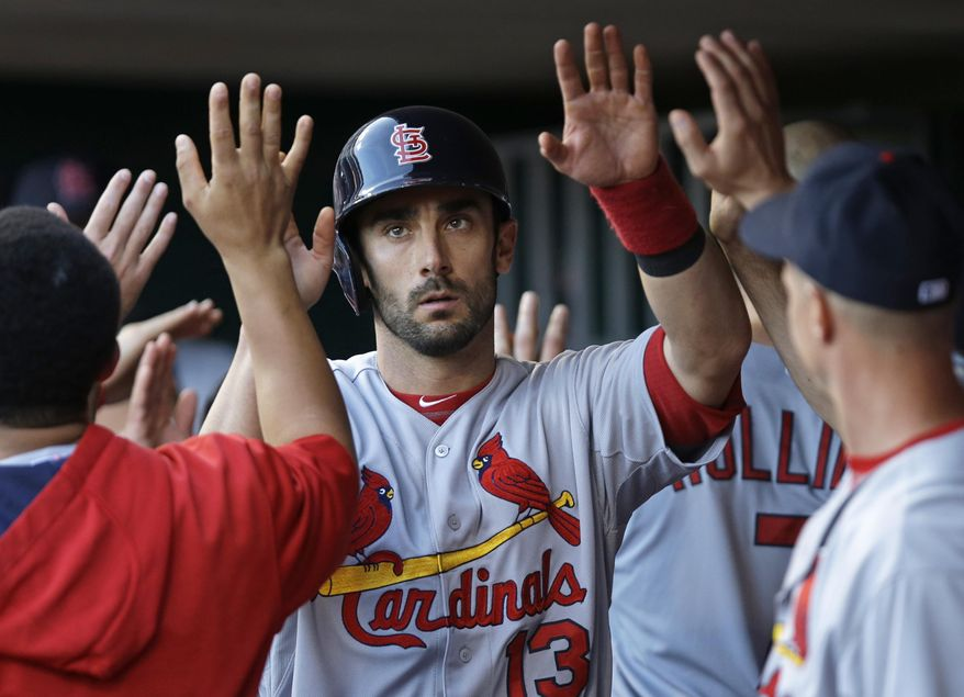 St. Louis Cardinals' Matt Carpenter (13) is congratulated in the dugout after scoring on a hit by Allen Craig in the fourth inning of a baseball game against the Cincinnati Reds, Friday, May 23, 2014, in Cincinnati. (AP Photo/Al Behrman)
