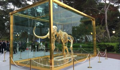 """In this photo taken on Thursday, May 22, 2014, British artist Damien Hirst's latest piece entitled """"Gone but Not Forgotten"""", which features the gilded skeleton of a woolly mammoth in a steel and glass vitrine, is displayed at an amfAR event in Cap d'Antibes, southern France. Famed British artist Damien Hirst created the gilded woolly mammoth skeleton encased in a gold tank to be auctioned off at the annual amfAR Cinema Against AIDS gala. (AP Photo/Nekesa Moody)"""