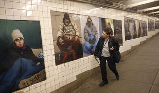 A woman cranes her neck as she passes by some of photographer Andres Serrano's portraits of homeless New Yorkers currently on display at the West 4th Street subway station in New York, Wednesday, May 21, 2014.  Best known for his controversial image of a crucifix dunked in his own urine, Serrano chose to show his portraits in some of the very places his unassuming subjects often populate_a subway station, a park and a church. (AP Photo/Kathy Willens)
