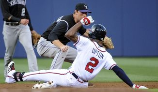 Atlanta Braves' B.J. Upton (2) safely slides into second base on a double as Colorado Rockies' DJ LeMahieu turns to try to tag him during the first inning of a baseball game Friday, May 23, 2014, in Atlanta. (AP Photo/David Tulis)