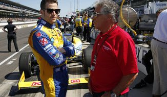 Marco Andretti, left, talks with his grandfather and 1969 Indy 500 champion Mario Andretti before the start of the final day of practice for the Indianapolis 500 IndyCar auto race at the Indianapolis Motor Speedway in Indianapolis, Friday, May 23, 2014. The 98th running of the Indianapolis 500 is Sunday. (AP Photo/Tom Strattman)