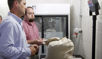 Benson Bell, executive director for Consumer and Environmental Protection, left, and Adam Watson, program coordinator, weigh a bag of hemp seed Friday, May 23, 2014 at the Kentucky Department of Agriculture in Frankfort. Hemp seeds that produced a drawn-out legal fight were freed from confinement and delivered Friday to Kentucky's Agriculture Department for experimental plantings, marking a limited comeback for the non-intoxicating cousin of marijuana. The seeds from Italy that drew so much suspicion from federal drug officials were unceremoniously unloaded from a UPS truck and then weighed by state agriculture officials. The shipment featuring 13 seed varieties came in at 286 pounds. (AP Photo/The Courier-Journal, James Crisp)
