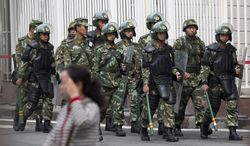 Paramilitary policemen with shields and batons patrol near the People's Square in Urumqi, China's northwestern region of Xinjiang, Friday, May 23, 2014. A day after the attack in Xinjiang's capital of Urumqi, survivors told of their terror during the attack and said they no longer feel insulated from a long-simmering insurgency against Chinese rule, which has struck their city twice in recent weeks. While the perpetrators haven't been named, Chinese authorities have blamed recent attacks on radical separatists from the country's Muslim Uighur minority. (AP Photo/Andy Wong)