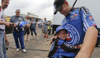 Funny Car driver Robert Height gets a hug from 8-year-old fan Lincoln Thompson prior to his first run of the day at the NHRA Kansas Nationals drag races at Heartland Park in Topeka, Kan., on Friday, May 23, 2014. (AP Photo/Topeka Capital-Journal,Chris Neal)