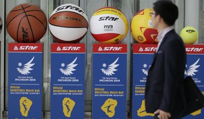A man walks by advertisement displays of the official balls for 2014 Incheon Asian Games at 2014 Incheon Asian Games Organizing Committee in Incheon, west of Seoul, South Korea, Friday, May 23, 2014. North Korea says it will enter the Asian Games hosted by South Korea in September, a glimmer of possible rapprochement in what has otherwise been rising animosity between the rivals in recent weeks. (AP Photo/Lee Jin-man)