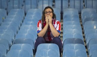 An Atletico supporter reacts after the team lost the Champions League final soccer match, taking place in Portugal, between Real Madrid and Atletico Madrid, in Madrid, Spain, Saturday, May 24, 2014. (AP Photo/Gabriel Pecot)
