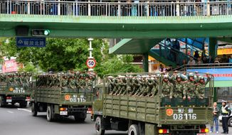 In this Friday, May 23, 2014 photo, trucks carrying paramilitary policemen move on a street in Urumqi, China's northwestern region of Xinjiang. Authorities on Saturday announced the first arrest in a bombing in China's Muslim northwest and said they were launching a yearlong anti-terrorism crackdown. (AP Photo/Kyodo News) JAPAN OUT, CREDIT MANDATORY