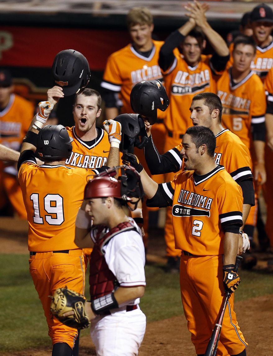 Oklahoma State celebrate a 3-run home run by Aaron Cornell (19) in the eighth inning near Oklahoma catcher Anthony Hermelyn (9) during an NCAA baseball game between Oklahoma and Oklahoma State in the Big 12 baseball tournament at the Chickasaw Bricktown Ballpark in Oklahoma City, Friday, May 23, 2014. (AP Photo/ The Oklahoman, Nate Billings)