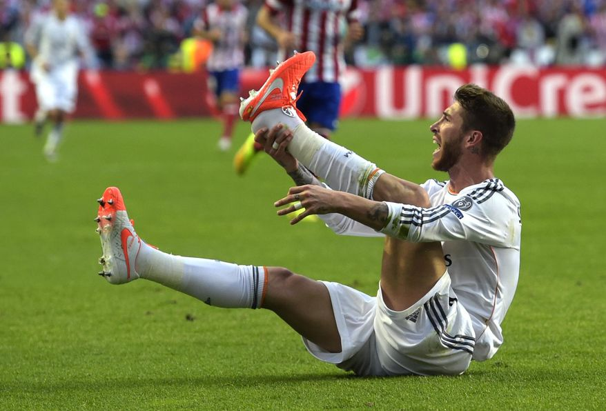 Real's Sergio Ramos, holds his foot,  during the Champions League final soccer match between Atletico Madrid and Real Madrid, at the Luz stadium, in Lisbon, Portugal, Saturday, May 24, 2014. (AP Photo/Manu Fernandez)