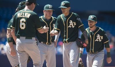 Oakland Athletics starting pitcher Jesse Chavez, second from right, hands the ball to manager Bob Melvin before getting pulled  in the sixth inning of a baseball game against the Toronto Blue Jays  in Toronto on Saturday, May 24, 2014.(AP Photo/The Canadian Press, Darren Calabrese)