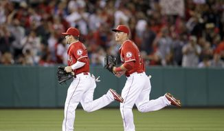 Los Angeles Angels' Collin Cowgill, left, and Mike Trout head back to the dugout after the top of the fifth inning of a baseball game against the Kansas City Royals on Friday, May 23, 2014, in Anaheim, Calif. (AP Photo/Jae C. Hong)