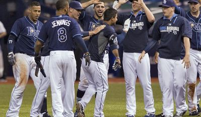 Tampa Bay Rays congratulate Cole Figueroa, center, after his game-winning base hit off Boston Red Sox reliever Burke Badenhop during the ninth inning of a baseball game Friday, May 23, 2014 in St. Petersburg, Fla. The Rays defeated the Red Sox 1-0. (AP Photo/Steve Nesius)