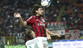 AC Milan defender Cristian Zaccardo, right, challenges for the ball with Sassuolo forward Gaetano Masucci during the Serie A soccer match between AC Milan and Sassuolo at the San Siro stadium in Milan, Italy, Sunday, May 18, 2014. (AP Photo/Antonio Calanni)