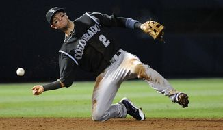 Colorado Rockies shortstop Troy Tulowitzki loses the ball on an attempted force out of Atlanta Braves' Tyler Pastornicky during the seventh inning of a baseball game Friday, May 23, 2014, in Atlanta. (AP Photo/David Tulis)