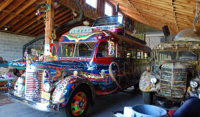 The original 1939 International bus dubbed Further and ridden on a cross-country trip in 1964 by author Ken Kesey and his friends, the Merry Pranksters, right, sits in a barn in Pleasant Hill, Ore., on May 14, 2014. Next to it, left, is a newer version of the bus that Kesey's son, Zane, plans to put back on the road for a 50th anniversary commemoration of the trip that became an icon of the psychedelic 1960s. (AP Photo/Jeff Barnard)