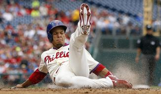 Philadelphia Phillies' Cesar Hernandez slides into home plate to score on a single by Ben Revere during the second inning of a baseball game against the Los Angeles Dodgers, Saturday, May 24, 2014, in Philadelphia. (AP Photo/Matt Slocum)