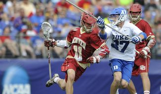 Denvers' Jack Bobzien drives to the goal as Duke's Casey Carroll defends in the first half of an NCAA semi-final lacrosse game Saturday, May 24, 2014, in Baltimore. (AP Photo/Gail Burton)