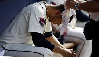 Atlanta Braves' Andrelton Simmons has a wet towel draped over his head by trainer Jim Lovell as he sits in the dugout in the fourth inning of a baseball game against the Colorado Rockies, Saturday, May 24, 2014, in Atlanta. (AP Photo/David Goldman)